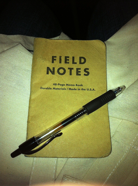 Photo of a worn Field Notes notebook with a black pen